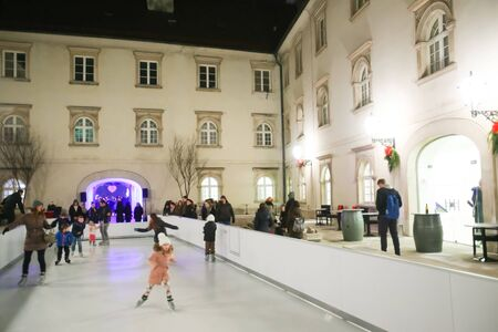 ZAGREB, CROATIA - DECEMBER 1th, 2016: Advent time in city center of Zagreb, Croatia. People ice skating at the synthethic ice rink in the ornate Art gallery Klovicevi Dvori in the upper old town.