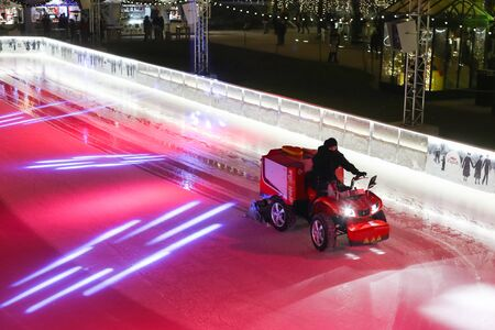 ZAGREB, CROATIA - DECEMBER 23, 2016: A man smoothing the ice with the ice resurfacer at the city ice skating rink at Advent time in King Tomislav Park in Zagreb, Croatia.