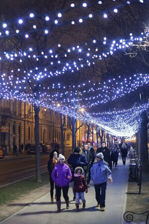 advent time: ZAGREB, CROATIA - DECEMBER 23rd, 2016: Advent time in city center of Zagreb, Croatia. People walking down the illuminated plane tree alley in the ornate King Tomislav Square.