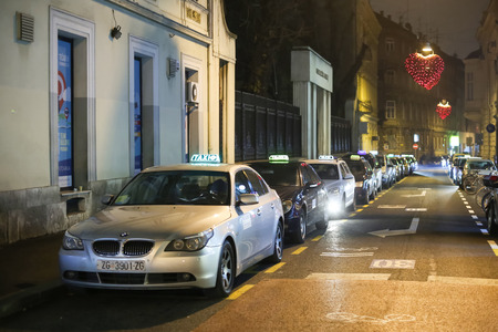 advent time: ZAGREB, CROATIA - DECEMBER 23rd, 2016: Advent time in city center of Zagreb, Croatia. Taxi station with lined up taxi cars in the decorated Gajeva street in center of Zagreb, Croatia.