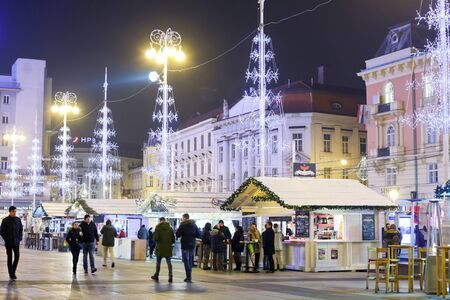 advent time: ZAGREB, CROATIA - DECEMBER 23rd, 2016: Advent time in city center of Zagreb, Croatia. People walking on ornated central Jelacic Square.
