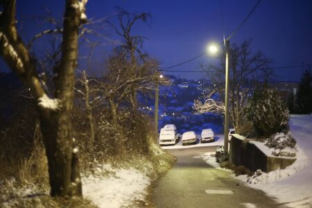 A view of parked cars on the street in village covered in snow at sunset. Stock Photo