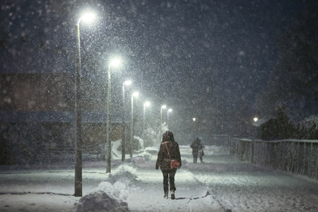 A rear view of a woman walking in the illuminated street covered with snow during strong snowfall. Stock Photo