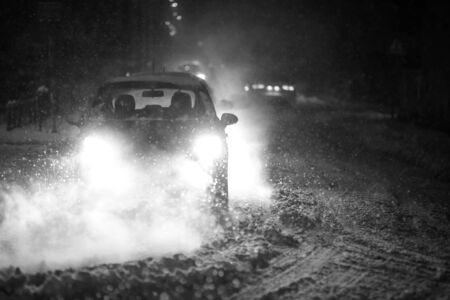 Cars driving on the road in the aggravated traffic due to strong snowfall.