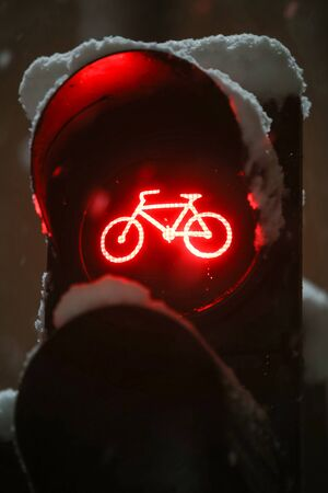 A close up of scoreboad showing red light for bicycles during snowfall.