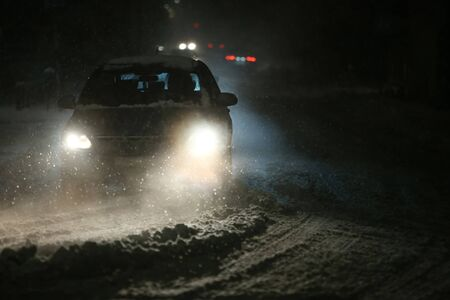 Cars driving on the road in the aggravated traffic due to strong snowfal.