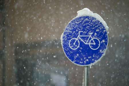 A sign for bicycle path covered in snow during snowfall. Stock Photo