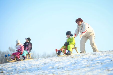 ZAGREB, CROATIA - JANUARY 15, 2017 : Children sledding down the hill in the presence of an adult woman at winter time in Zagreb, Croatia.