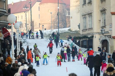 grade schooler: ZAGREB, CROATIA - JANUARY 15, 2017 : FIS World Snow Day for kids with free skiing and snowboarding lessons on the ski slope in Bakaceva street, on the road from the cathedral to the main square. Kids skiing on the slope with adults helping them.