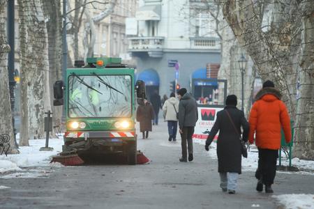 ZAGREB, CROATIA - JANUARY 15, 2017 : People walking in Zrinjevac park next to the street sweeper machine in Zagreb, Croatia.