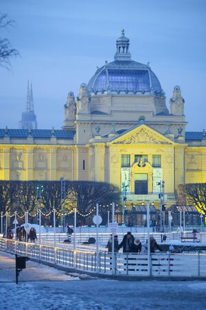 ZAGREB, CROATIA - JANUARY 15, 2017 : A view of Art Pavilion at sunset with people skating in the city ice skating rink in King Tomislav Square in Zagreb, Croatia.