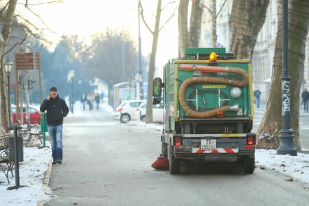 ZAGREB, CROATIA - JANUARY 15, 2017 : A man walking next to the street sweeper machine in city center in Zagreb, Croatia.