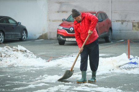 ZAGREB, CROATIA - JANUARY 15, 2017 : A man cleaning the snow off the parking lot with a shovel in Zagreb, Croatia. Stock Photo - 71948531