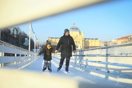 ZAGREB, CROATIA - JANUARY 15, 2017 : A view through the fence of a boy and a girl ice skating in the city ice skating rink in King Tomislav Square in Zagreb, Croatia. Editorial