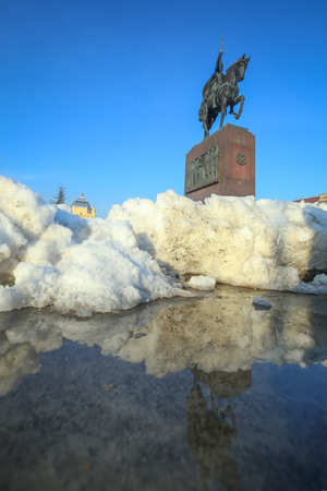 A pile of snow reflecting in the wet pavement with the statue of King Tomislav in the background at King Tomislav Square in Zagreb, Croatia.
