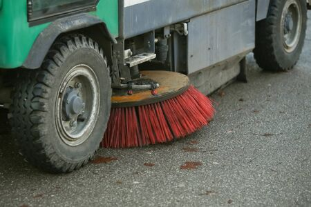 A close up of wheels and brush of a street sweeper machine. Stock Photo