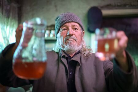 A front view of an old man with a pitcher of wine and a glass.