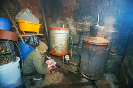 An Older Man Making Homemade Brandy In The Boilers In His Shed ...