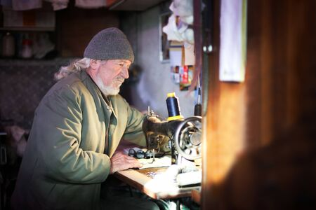 A senior adult man sewing a piece of cloth on a sewing machine.