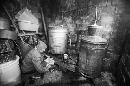 An older man making homemade brandy in the boilers in his shed. Stock Photo