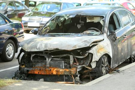 De buitenkant van een uitgebrande auto op een parkeerplaats.