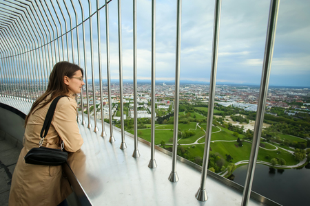 MUNICH, GERMANY - MAY 6, 2017 : A woman looking at the cityscape at the observation platform of the Olympic Tower in the Olympic Park in Munich, Germany. Editorial