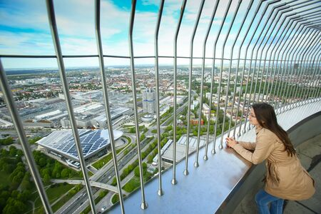 MÜNCHEN, DEUTSCHLAND - 6. MAI 2017: Eine Frau, die das Stadtbild mit BMW-Museum auf die Aussichtsplattform des olympischen Turms im Olympiapark in München, Deutschland betrachtet. Standard-Bild - 80137896
