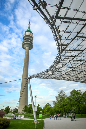 MUNICH, GERMANY - MAY 6, 2017 : A low angle view of the Olympic Tower in the Olympic Park with people walking in Munich, Germany.