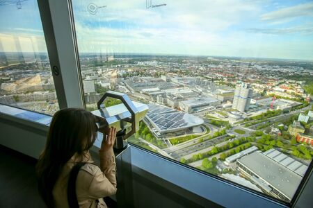 MUNICH, GERMANY - MAY 6, 2017 : A woman looking at the cityscape through the binoculars at the observation platform of the Olympic Tower in the Olympic Park in Munich, Germany. Editorial