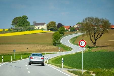 NANDLSTADT, ドイツ - 10.05.2017: ババリア、ドイツの春の制限速度歌う 70 および耕されたフィールドの横にある道路上の車。