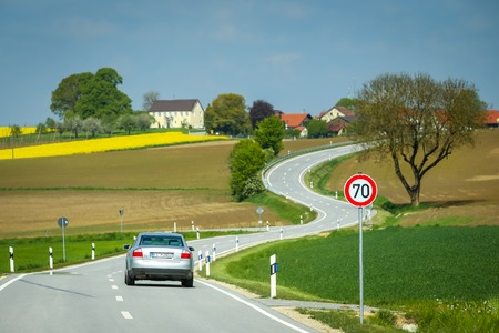 NANDLSTADT, GERMANY - 10.05.2017 : A car on the road passing next to speed limit sing of 70 and cultivated fields in spring in Bavaria, Germany. Redakční