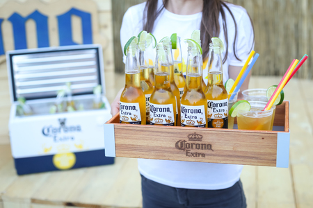 ZAGREB, CROATIA - JUNE 28, 2017 : Waitress holding wooden box full of Corona Extra beer bottles and cocktails on the Corona Sunsets Session party on the roof of Zagreb Dance Center in Zagreb, Croatia.