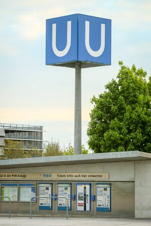 u bahn: MUNCHEN, GERMANY - MAY 9, 2017 : A large U- Bahn subway sign with ticket cashier in Munich, Germany. About 350 million passengers ride the U-Bahn every year.