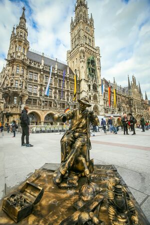 entertainers: MUNICH, GERMANY - MAY 9, 2017 : A street entertainer disguised as a sculpture fountain with people in the background sightseeing New Town Hall in Munich, Germany.