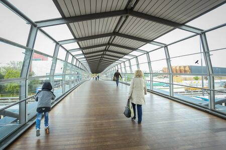 u bahn: MUNCHEN, GERMANY - MAY 9, 2017 : People walking in the glass tunnel from the Frottmaning train station on the U6 subway line in Munich, Germany. About 350 million passengers ride the U-Bahn every year.