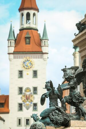 MUNICH, GERMANY - MAY 9, 2017 : The pedestal of Virgin Mary Statue with putto statue and the Old Town Hall at Marienplatz in Munich, Germany.