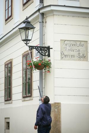 ZAGREB, CROATIA - MAY 20, 2017 : A street lamp lighter lighting up the gas street lamp on Gradec in Zagreb, Croatia.
