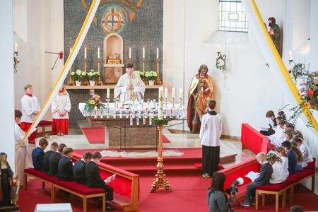 NANDLSTADT, DEUTSCHLAND - 7. MAI 2017: Der Priester, der die Masse an der ersten Kommunion mit den Jungen und Mädchen sitzen in der Front in Nandlstadt, Deutschland hält. Standard-Bild - 81987024