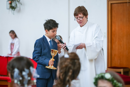 NANDLSTADT, GERMANY - MAY 7, 2017 : A young boy reading communion verses from the paper held by the priests assistant at the first communion in Nandlstadt, Germany. Éditoriale