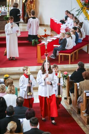 NANDLSTADT, GERMANY - MAY 7, 2017 : A group of altar servers holding cross with Jesus and candles on stands and walking down the isle in church at the first communion in Nandlstadt, Germany.