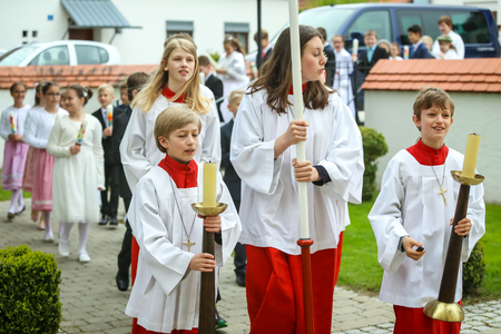 NANDLSTADT, GERMANY - MAY 7, 2017 : A group of altar servers holding candles on stands and leading the communicants at the first communion in Nandlstadt, Germany.