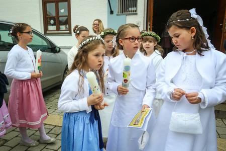 NANDLSTADT, ALLEMAGNE - 7 MAI 2017: Un groupe de jeunes filles tenant des bougies et debout devant l'église lors de leur première communion à Nandlstadt, en Allemagne. Éditoriale