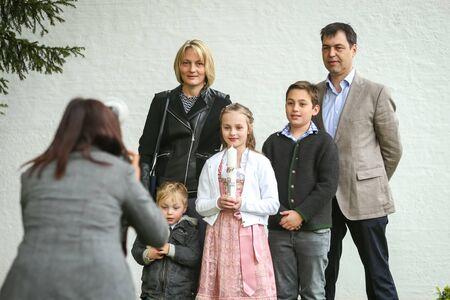NANDLSTADT, ALLEMAGNE - 7 MAI 2017: Une jeune fille avec une bougie posant avec sa famille à un photographe lors de la première communion à Nandlstadt, en Allemagne.