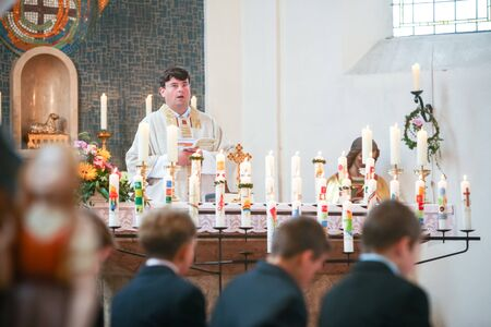 NANDLSTADT, GERMANY - MAY 7, 2017 : A priest holding the mass at the first communion with young boys sitting in first row in Nandlstadt, Germany. Éditoriale