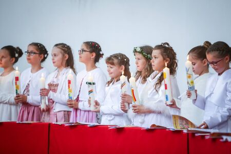 NANDLSTADT, GERMANY - MAY 7, 2017 : A group of young girls standing lined up in church and holding lighted candles at their first communion in Nandlstadt, Germany. Éditoriale