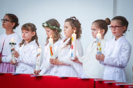 NANDLSTADT, ALLEMAGNE - 7 MAI 2017: Un groupe de jeunes filles alignées à l'église et tenant des bougies allumées lors de leur première communion à Nandlstadt, en Allemagne. Éditoriale