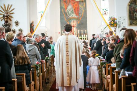 NANDLSTADT, ALLEMAGNE - 7 MAI 2017: Une vue arrière du prêtre qui se tient dans l'église avec un groupe de jeunes communicants entre des bancs pleins de personnes qui assistent à la première communion à Nandlstadt, en Allemagne. Éditoriale