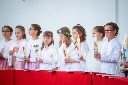 NANDLSTADT, ALLEMAGNE - 7 MAI 2017: Un groupe de jeunes filles alignées à l'église et tenant des bougies allumées lors de leur première communion à Nandlstadt, en Allemagne.