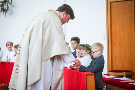 NANDLSTADT, GERMANY - MAY 7, 2017 : The priest giving young boys and girls the sacramental bread at their first communion in Nandlstadt, Germany. Éditoriale