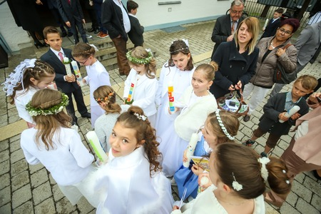 NANDLSTADT, GERMANY - MAY 7, 2017 : A group of children holding candles and adults standing in front of church at the first communion in Nandlstadt, Germany. Éditoriale